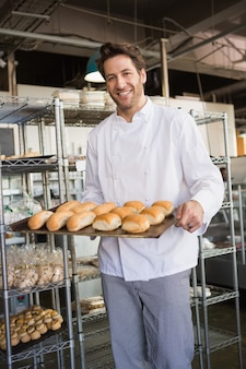 Panadero feliz que muestra la bandeja con pan en la panadería