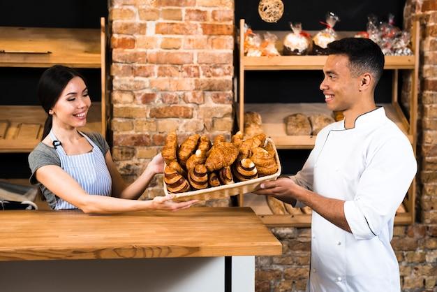 Panadero femenino y masculino que sostiene la cesta de croissant cocido al horno en la pastelería