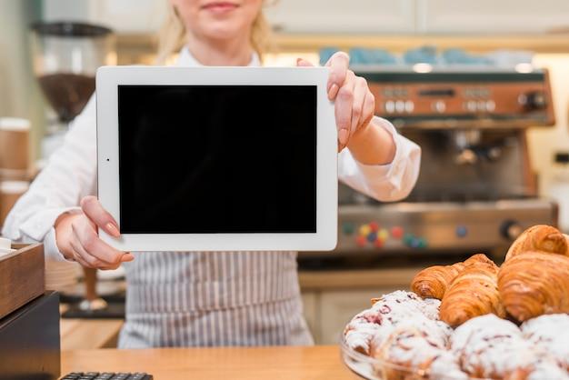 Panadero femenino mostrando tableta digital frente a croissant horneado en el mostrador
