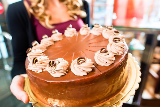 Panadero femenino que presenta la torta en confitería