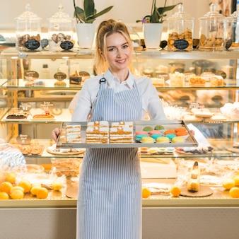 Panadero femenino que sostiene los macarrones y los pasteles frescos cocidos en la bandeja