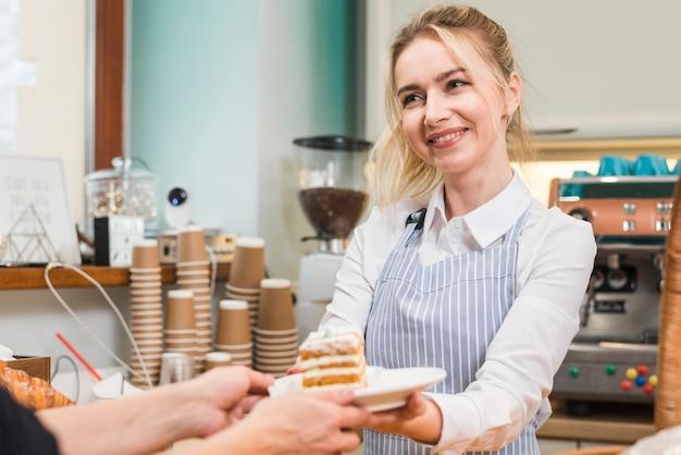 Panadero femenino sonriente que sirve la torta de los pasteles al cliente