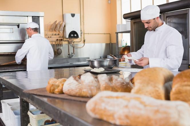 Panadero haciendo masa en un tazón en la cocina de la panadería