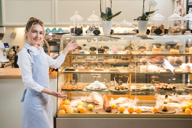 Panadero hembra presentando los diferentes pasteles en la vitrina transparente.