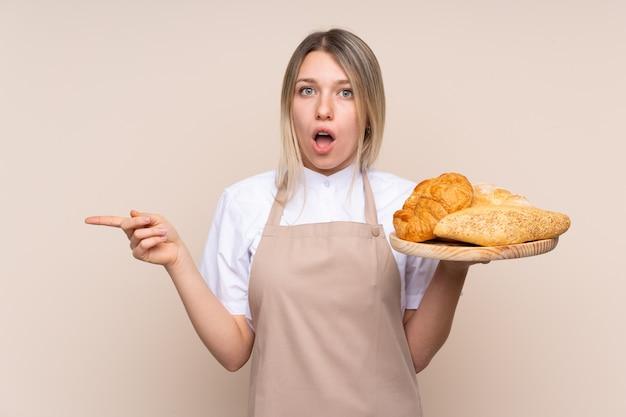 Panadero hembra sosteniendo una mesa con varios panes sorprendido y apuntando hacia el lado