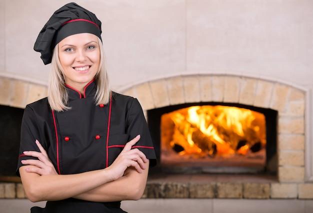 El panadero hermoso del cocinero está parado delante del horno.
