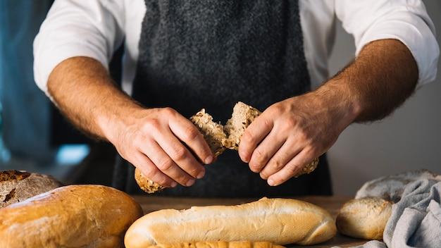Panadero hombre sosteniendo pan recién horneado en la panadería