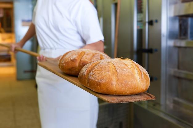 Panadero horneando pan mostrando el producto