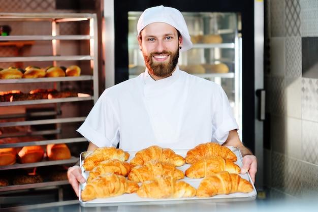 El panadero masculino hermoso sostiene una bandeja con los croissants franceses delante de una panadería y sonríe.