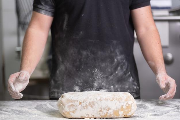 Panadero que amasa la masa fresca del pan crudo en la panadería.