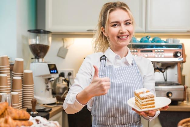 Panadero de sexo femenino feliz que lleva a cabo la rebanada de los pasteles en la placa blanca que muestra el pulgar encima de la muestra