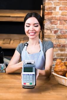 Panadero de sexo femenino feliz que sostiene el terminal del banco en tienda de la panadería
