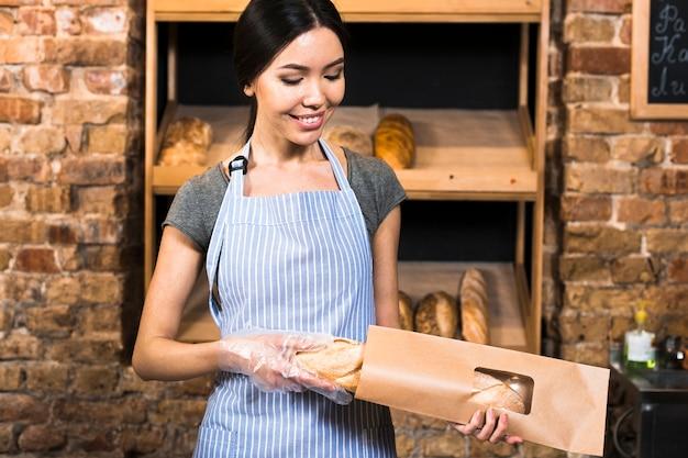 Panadero de sexo femenino joven sonriente que embala el pan del baguette en la bolsa de papel marrón en tienda