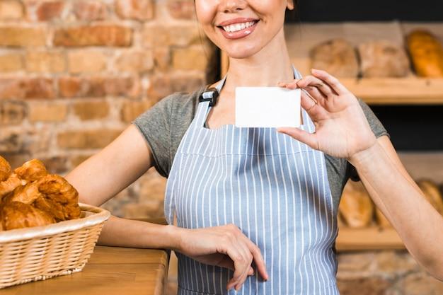 Panadero de sexo femenino joven sonriente que muestra la tarjeta de visita blanca en la tienda de la panadería