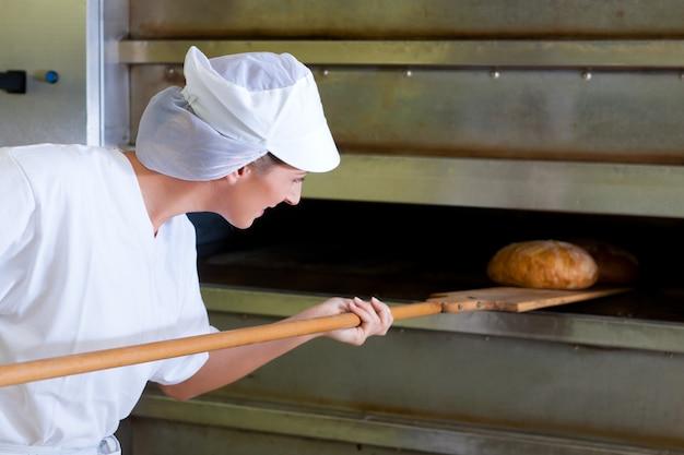 Panadero de sexo femenino que cuece el pan fresco en la panadería
