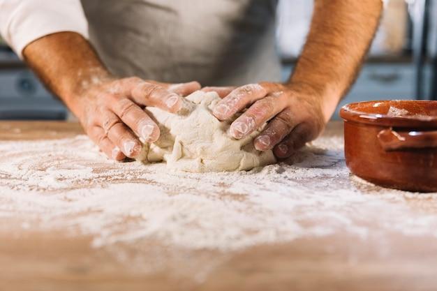Panadero de sexo masculino amasando la harina de la masa en la mesa de madera