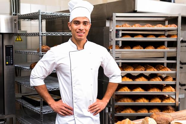 Panadero de sexo masculino hermoso joven en el uniforme blanco que se opone al estante de la hornada