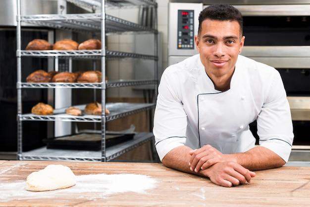 Panadero de sexo masculino de pie detrás de la mesa con masa en la panadería