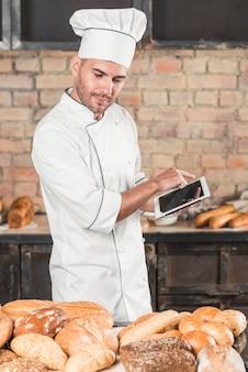 Panadero de sexo masculino que mira el surtido de panes usando la tableta digital