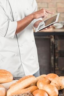 Panadero de sexo masculino que está parado detrás de la tabla con panes usando la tableta digital