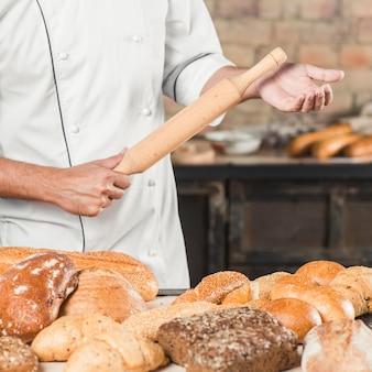 Panadero de sexo masculino que sostiene el rodillo de madera con la variedad de panes en la tabla