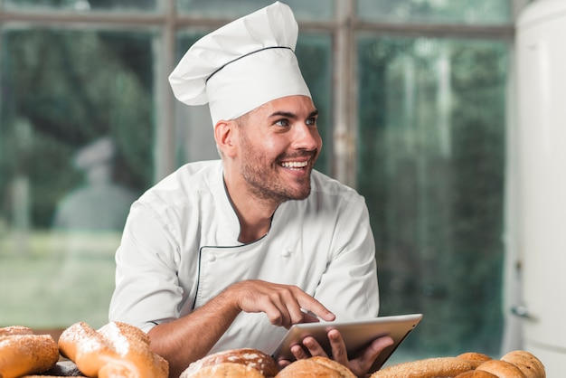 Panadero de sexo masculino con tableta digital con panes horneados