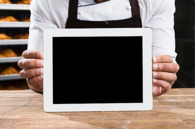 Un panadero de sexo masculino en uniforme que sostiene la pequeña tableta digital en blanco en la mesa de madera