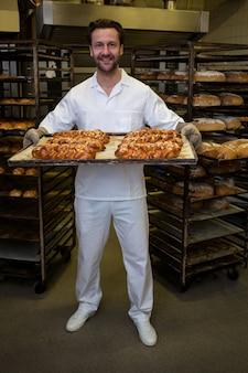 Panadero sonriendo hogaza de bollos recién horneados que sostiene retorcidos