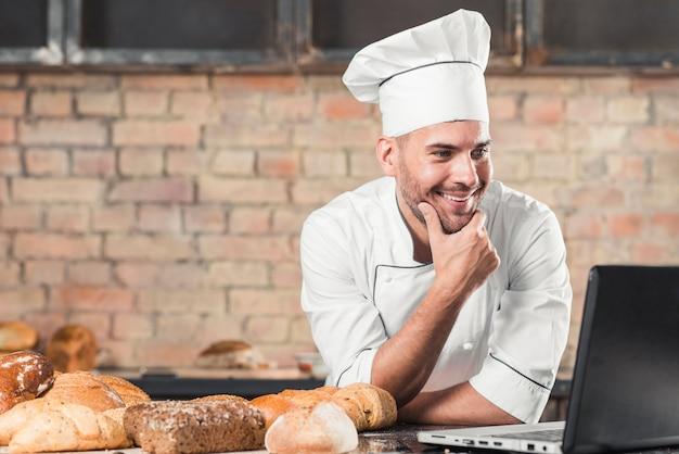 Panadero sonriente que mira la computadora portátil sobre el worktop de la cocina con panes cocidos