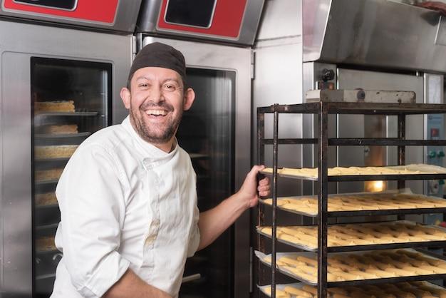 Panadero sonriente que pone un estante de pasteles en el horno en panadería o pastelería.