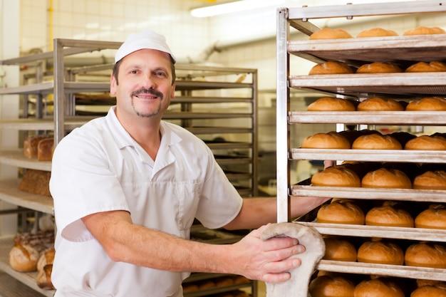 Panadero en su panadería horneando pan