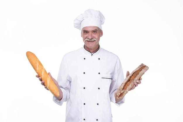 Panadero viejo profesional en uniforme sosteniendo baguettes con pan mientras permanece en la pared blanca