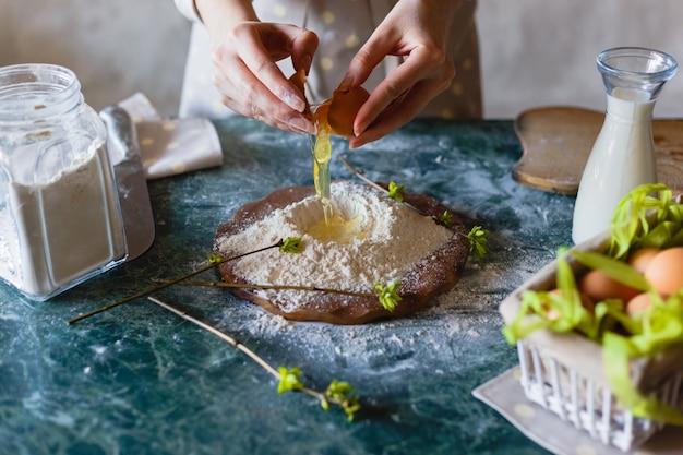 Panadero vierte el huevo en el embudo de la harina.
