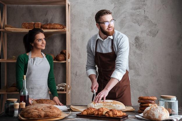 Panaderos de pareja amorosa alegre mirando a un lado.