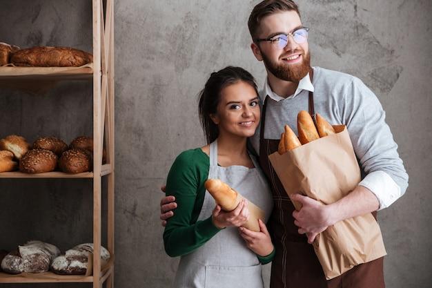 Panaderos de pareja amorosa alegre con pan en las manos.