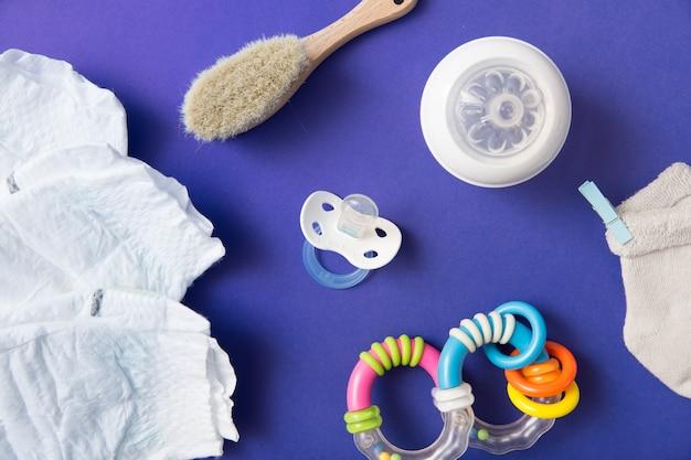 Pañal; cepillo; chupete; botella de leche; calcetín y sonajero sobre fondo azul