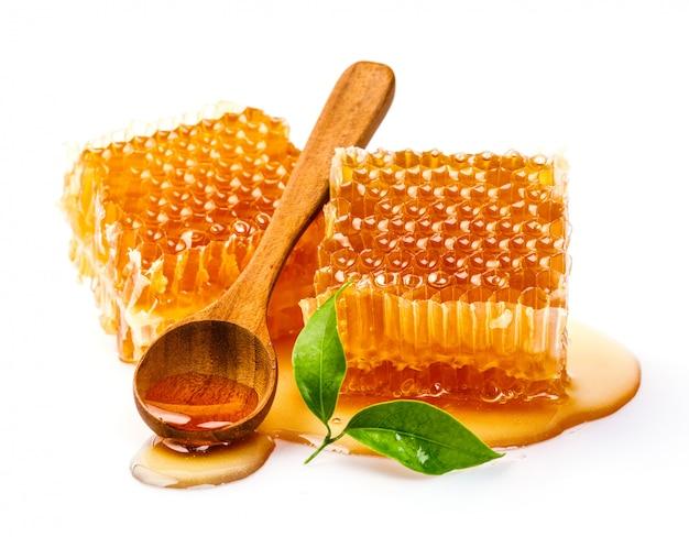 Panal con cuchara de miel y hojas aisladas sobre fondo blanco.