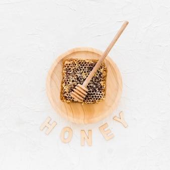 Panal con cucharón de miel de madera en un plato con miel de texto