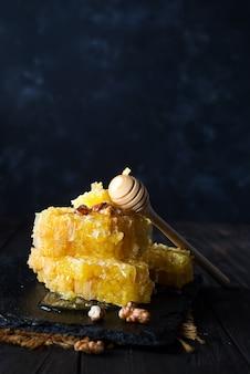 Panal con cucharón de miel y nueces sobre oscuro