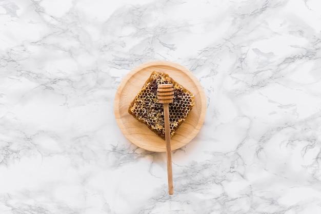Panal con cucharón de miel en plato de madera
