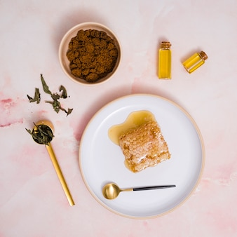 Panal y miel en placa de cerámica con productos cosméticos contra fondo texturado rosa