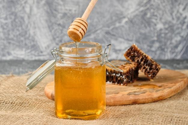 Panal con miel sobre una tabla de madera, con una cuchara para miel vierte lentamente enfoque selectivo de miel