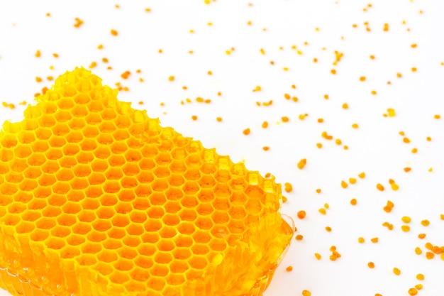 Panal de oro y polen amarillo sobre un blanco