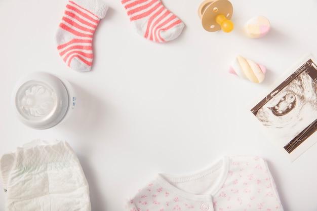Pañal; ropa de bebé; malvavisco; calcetines; chupete; foto de sonografía y botella de leche sobre fondo blanco