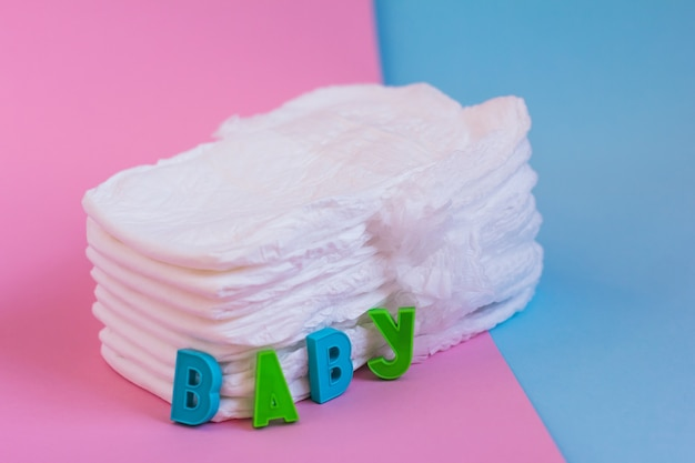 Pañales para bebés en una superficie azul y rosa con letras bebé, espacio de copia