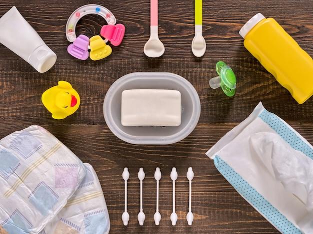 Pañales japoneses, toallitas húmedas, jabón, talco para bebés, crema, tither, bastoncillos de algodón, cucharas, chupete y patito sobre fondo de madera marrón oscuro