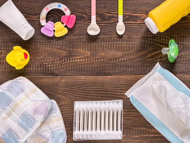 Pañales japoneses, toallitas húmedas, talco para bebés, crema, tither, bastoncillos de algodón, cucharas, chupete y patito sobre fondo de madera marrón oscuro con espacio de copia
