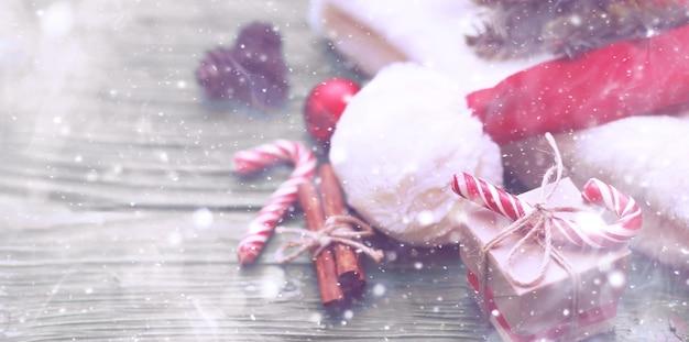 La pancarta navideña. diseño de año nuevo, una composición de caja de regalo, copos de nieve, gorro de papá noel, caramelo, ramas de abeto y confeti brillante. plantilla, en blanco para un póster, tarjetas de felicitación, encabezado