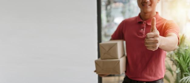 Pancarta panorámica hombre de servicio de entrega en uniforme rojo mostrando los pulgares hacia arriba y sosteniendo la caja de paquetería lista para enviar al cliente en casa