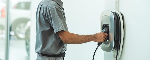 Pancarta y portada de la escena de closeup cargando el auto eléctrico en el centro de servicio de mantenimiento que es parte del concepto de sala de exposición, económico y tecnológico para el mundo seguro